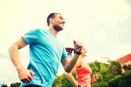 Foto de fitness, sport, friendship and lifestyle concept - smiling couple running outdoors - Imagen libre de derechos
