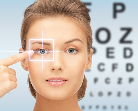 Photo pour medicine, eyesight control, laser correction, people and health concept - beautiful young woman pointing finger to her eye and over blue background with eye chart - image libre de droit