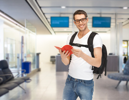 Photo for travel, education, tourism and people - smiling student with backpack and book at airport - Royalty Free Image