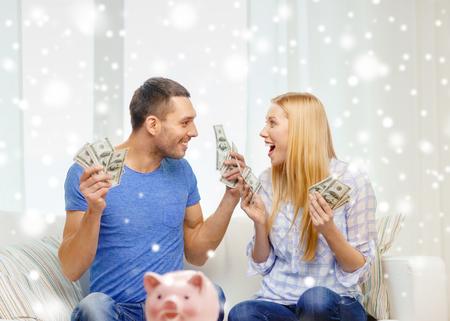 Foto de love, family, finance, money and happiness concept - happy couple with cash money and piggybank cheering at home - Imagen libre de derechos