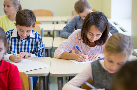 Foto de education, elementary school, learning and people concept - group of school kids with pens and notebooks writing test in classroom - Imagen libre de derechos