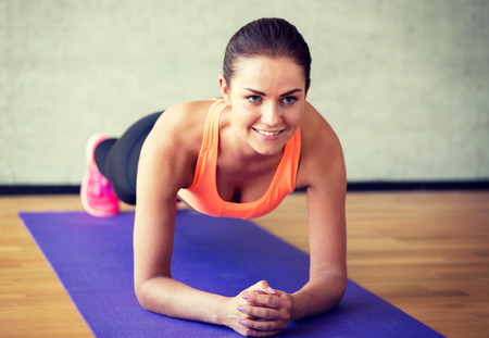 Photo for fitness, sport, training and lifestyle concept - smiling woman doing exercises on mat in gym - Royalty Free Image