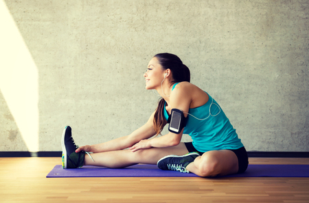 Photo pour fitness, sport, training and lifestyle concept - smiling woman stretching leg on mat in gym - image libre de droit