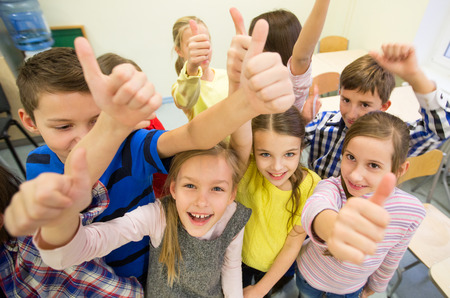 Foto de education, elementary school, learning, gesture and people concept - group of school kids and showing thumbs up in classroom - Imagen libre de derechos