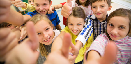 Photo pour education, elementary school, learning, gesture and people concept - group of school kids and showing thumbs up in classroom - image libre de droit