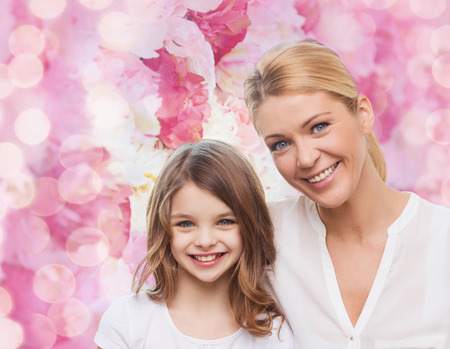 family, childhood, happiness and people - smiling mother and little girl over pink lights background