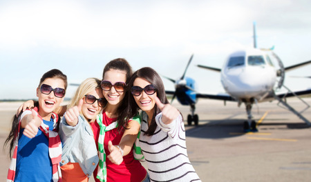 Photo for travel, holidays, vacation, happy people concept - smiling teenage girls or young women showing thumbs up at airport - Royalty Free Image