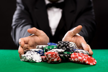Foto de casino, gambling, poker, people and entertainment concept - close up of poker player with chips at green casino table - Imagen libre de derechos