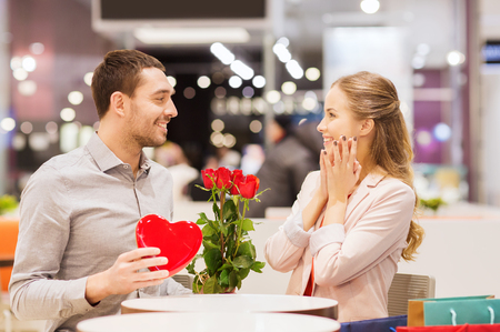 Photo for love, romance, valentines day, couple and people concept - happy young man with red flowers giving present to smiling woman at cafe in mall - Royalty Free Image