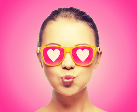 Foto de love, happiness, valentines day, face expressions and people concept - portrait of teenage girl in pink sunglasses with hearts blowing kiss - Imagen libre de derechos