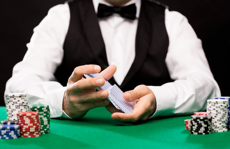 Foto de casino, gambling, poker, people and entertainment concept - close up of holdem dealer shuffling playing cards deck and chips on green table - Imagen libre de derechos
