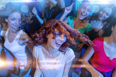 Photo pour party, holidays, celebration, nightlife and people concept - smiling friends dancing in club - image libre de droit