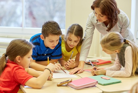 Photo pour education, elementary school, learning and people concept - teacher helping school kids writing test in classroom - image libre de droit