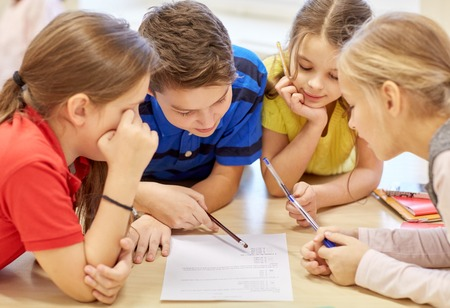 Foto de education, elementary school, learning and people concept - group of school kids with pens and papers writing in classroom - Imagen libre de derechos