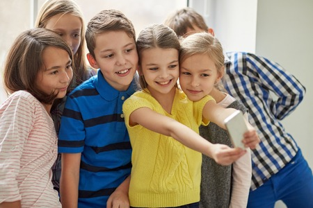 Photo pour education, elementary school, drinks, children and people concept - group of school kids taking selfie with smartphone in corridor - image libre de droit