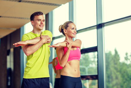 Photo for sport, fitness, lifestyle and people concept - smiling man and woman stretching in gym - Royalty Free Image