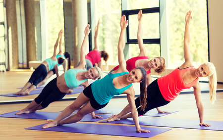 Photo pour sport, meditation and lifestyle concept - smiling women meditating on mat in gym - image libre de droit