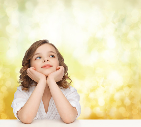 Photo pour children, childhood, holidays and happy people concept - beautiful girl sitting at table, looking up and dreaming over yellow lights background - image libre de droit