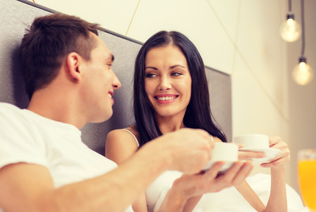 Photo pour hotel, travel, relationships and happiness concept - smiling couple having breakfast in bed in hotel room - image libre de droit