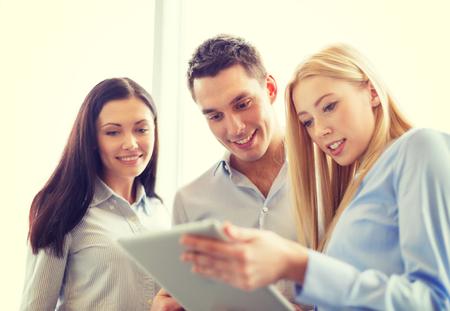 Foto de business and office concept - smiling business team working with tablet pc in office - Imagen libre de derechos