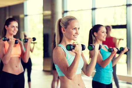 Foto de fitness, sport, training, gym and lifestyle concept - group of women with dumbbells in gym - Imagen libre de derechos