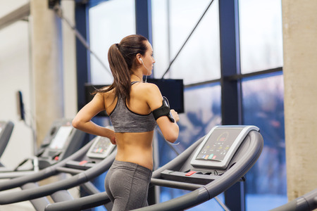 sport, fitness, lifestyle, technology and people concept - woman with smartphone or player and earphones exercising on treadmill in gym