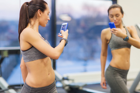 Foto de sport, fitness, lifestyle, technology and people concept - young woman with smartphone taking mirror selfie in gym - Imagen libre de derechos