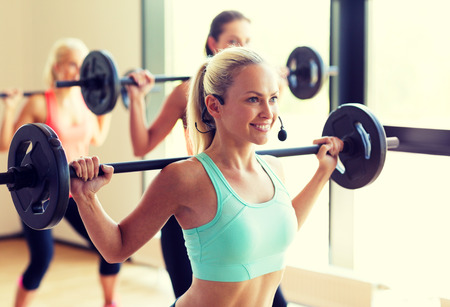 Foto per fitness, sport, training and lifestyle concept - group of women with barbells in gym - Immagine Royalty Free