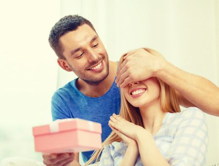 Photo pour love, holiday, celebration and family concept - smiling man surprises his girlfriend with present at home - image libre de droit