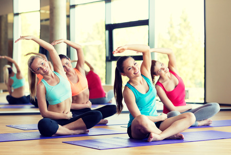 Foto de fitness, sport, training and lifestyle concept - group of smiling women stretching in gym - Imagen libre de derechos