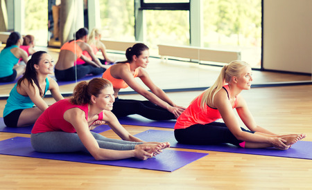 Photo pour fitness, sport, training and lifestyle concept - group of smiling women stretching in gym - image libre de droit