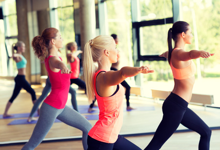 Foto für fitness, sport, training and lifestyle concept - group of smiling women stretching in gym - Lizenzfreies Bild