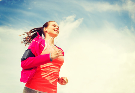 Photo pour fitness, sport and lifestyle concept - smiling young woman with earphones running outdoors - image libre de droit
