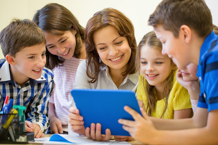 Photo for education, elementary school, learning, technology and people concept - group of school kids with teacher looking to tablet pc computer in classroom - Royalty Free Image