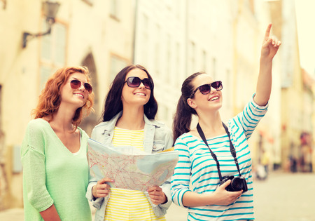 Foto de tourism, travel, leisure, holidays and friendship concept - smiling teenage girls with map and camera outdoors - Imagen libre de derechos