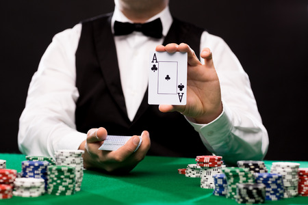 Photo pour casino, gambling, poker, people and entertainment concept - close up of holdem dealer with playing cards and chips on green table - image libre de droit