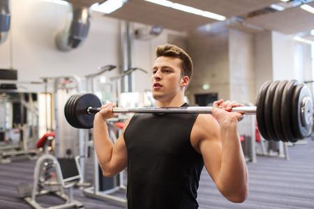 Foto de sport, bodybuilding, lifestyle and people concept - young man with barbell flexing muscles in gym - Imagen libre de derechos