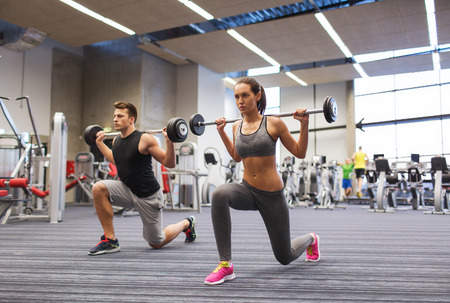 Photo pour sport, bodybuilding, lifestyle and people concept - young man and woman with barbell flexing muscles and making shoulder press lunge in gym - image libre de droit