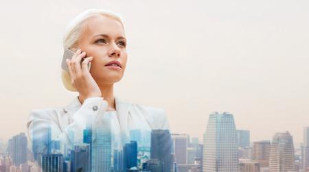 Foto de business, technology, communication and people concept - serious businesswoman with smartphone talking over city background - Imagen libre de derechos
