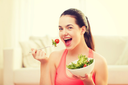 Foto de healt, dieting, home and happiness concept - smiling sporty teenage girl with green salad at home - Imagen libre de derechos