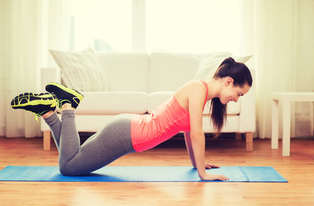 Foto de fitness, home and diet concept - smiling teenage girl doing push-ups at home - Imagen libre de derechos