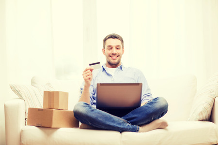 Photo pour technology, home and lifestyle concept - smiling man with laptop, credit card and cardboard boxes at home - image libre de droit