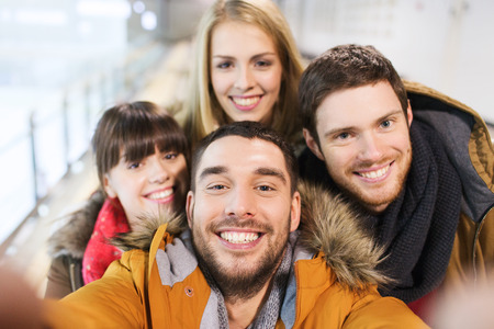 Photo for people, friendship, technology and leisure concept - happy friends taking selfie with camera or smartphone on skating rink - Royalty Free Image