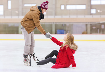 Photo pour people, friendship, sport and leisure concept - smiling man helping women to rise up on skating rink - image libre de droit
