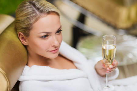 Photo pour people, beauty, lifestyle, holidays and relaxation concept - beautiful young woman in white bath robe lying on chaise-longue and drinking champagne at spa - image libre de droit