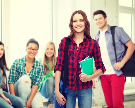 Foto de education and people concept - smiling female student with laptop bag and notebooks - Imagen libre de derechos