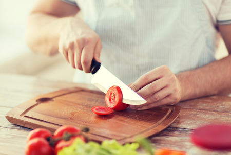 Foto per cooking and home concept - close up of male hand cutting tomato on cutting board with sharp knife - Immagine Royalty Free