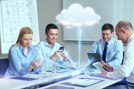 Photo for business, people, cloud computing and technology concept - smiling business team with smartphones, tablet pc computers working in office - Royalty Free Image