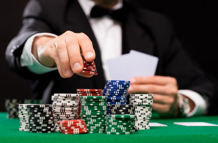 Foto de casino, gambling, poker, people and entertainment concept - close up of poker player with playing cards and chips at green casino table - Imagen libre de derechos