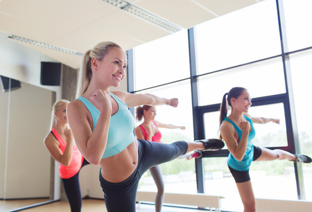 Foto de fitness, sport, people, martial arts and gym concept - group of women working out and standing in battle stance - Imagen libre de derechos